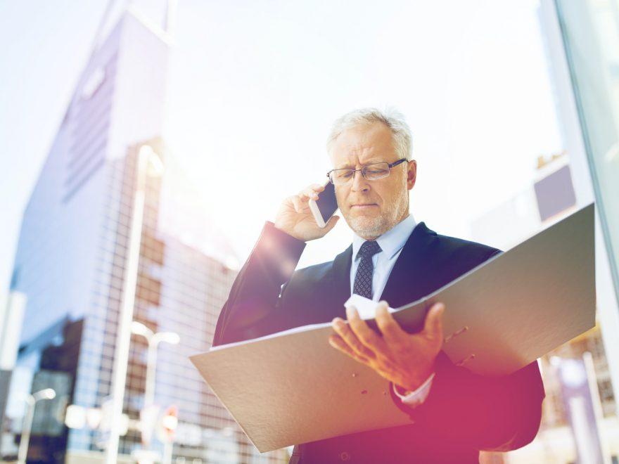 senior businessman calling on smartphone in city