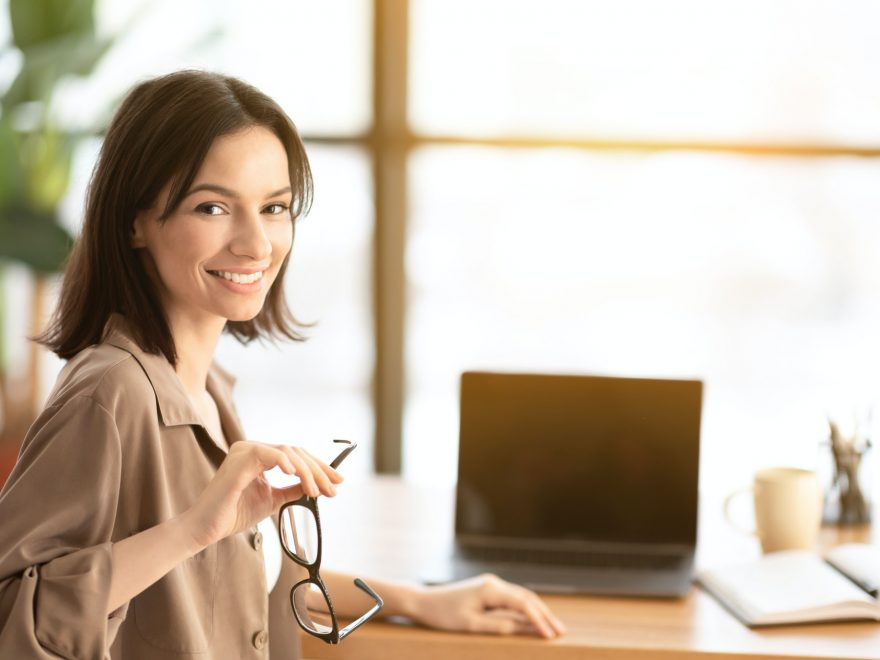 Smiling young worker with blank screen laptop